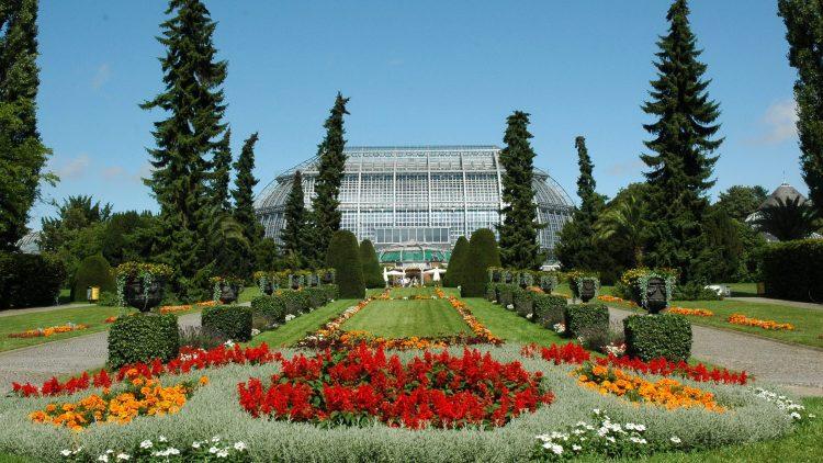 Blick auf das große Tropenhaus im Botanischen Garten Berlin mit bunten Blumenrabatten im Vordergrund
