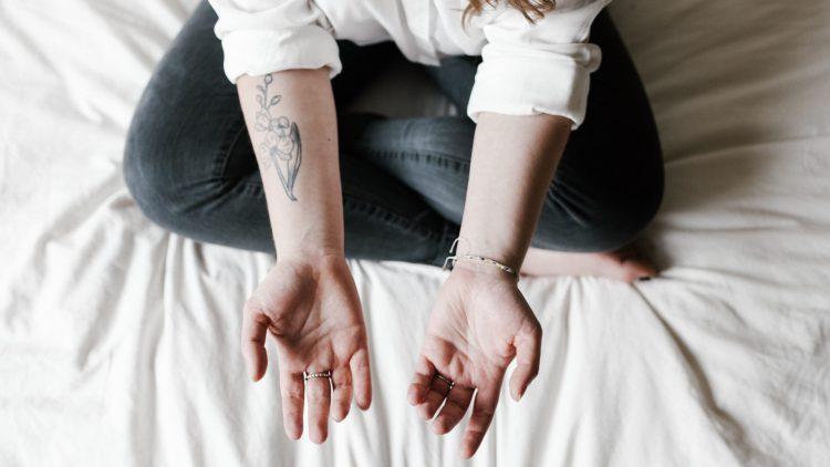 Frau mit Jeans und weißer Bluse sitzt auf Bett mit weißem Laken und hält Unterarme der Kamera über ihr entgegen, einer davon tätowiert