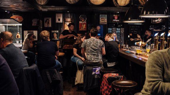 Menschen sitzen in Gruppen im Pub an Tischen und am Tresen