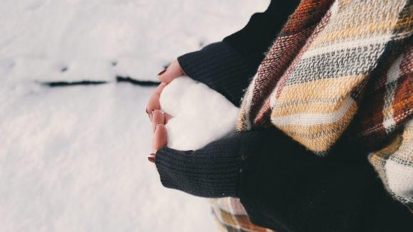 Frauenarme in Strickpullover mit Herz aus Schnee in den Händen
