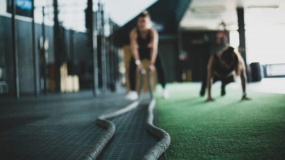 Zwei Frauen trainieren Crossfit, eine schwingt Seile, die andere macht eine Plank.
