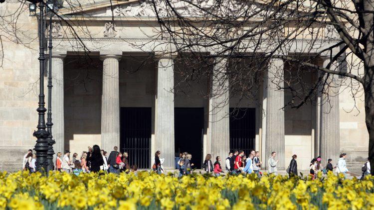 An blühen Narzissen und im Hintergrund dem Käthe-Kollwitz-Museum entlang gehen diese Berlin-Besucher