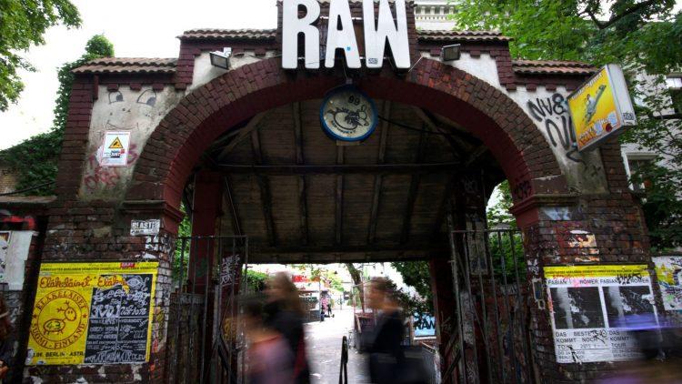 """Torbogen aus Backstein mit dem weißen Schriftzug """"RAW"""", Mauer ist mit Plakaten beklebt"""
