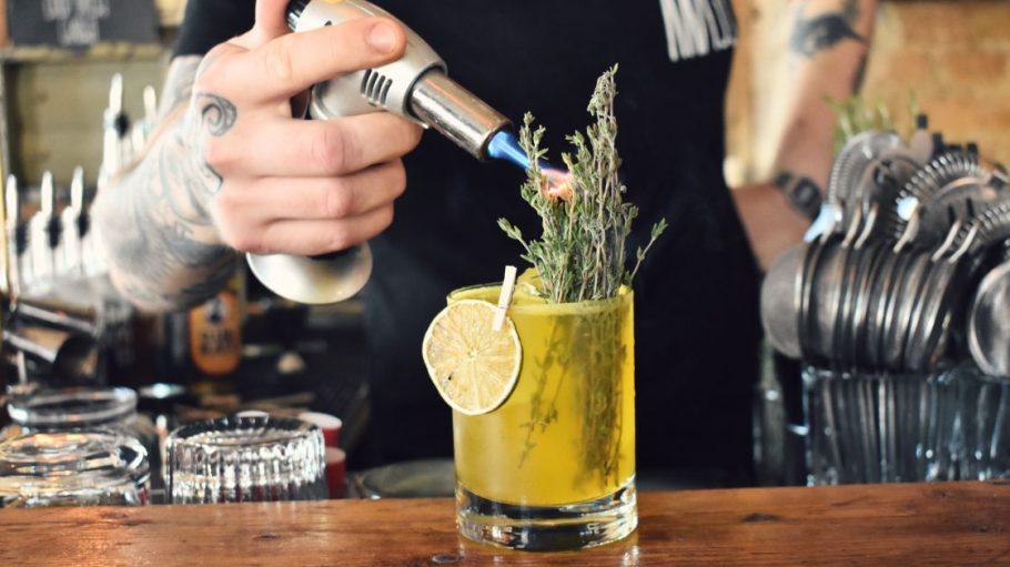 Barkeeper hält Flamme an Cocktail mit Zitronenscheibe und Thymian