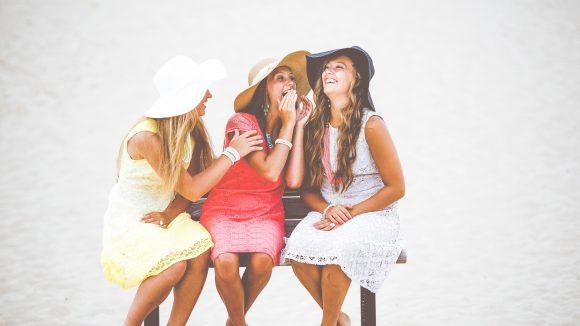 Drei Frauen mit schönen Kleidern in weiß, rot und gelb und Hüten sitzen zusammen auf einer Parkbank in Hoppegarten und lachen miteinander.