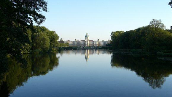 Schloss Charlottenburg von weiten fotografiert. Im Vordergrund der blaue See.