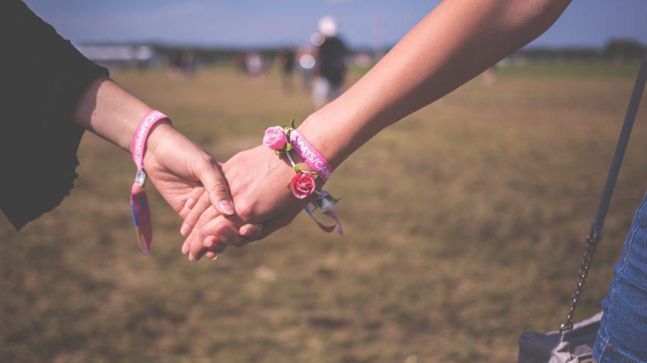 Zwei Frauen halten Händchen.