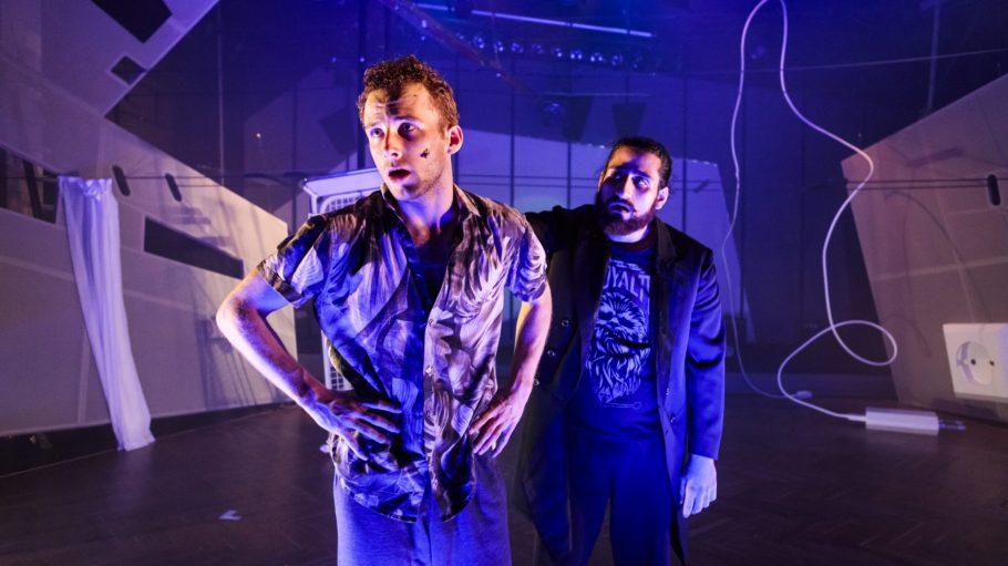 Die Schauspieler Sven Scheele und Armin Wahedi Yeganeh stehen in blauem Licht auf der Bühne der Neuköllner Oper