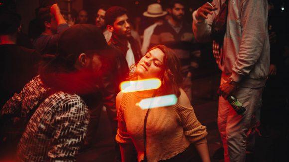 Frau lehnt sich bei Tanzen zu Mann nach vorne