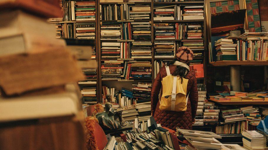 Frau mitgelben Rucksack steht vor einem großen Regal voller alter Bücher