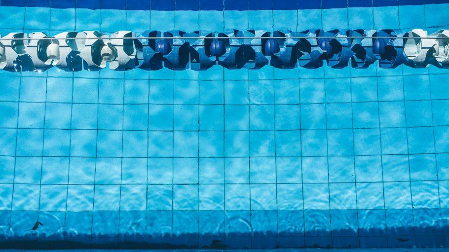 Nackte Männerfüße vor Freibad Schwimmbecken