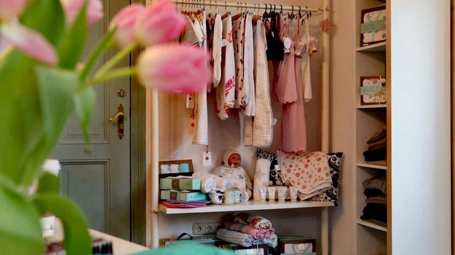 Ein Regal im Inneren des Ladens mit Babypuppe und Klamotten.
