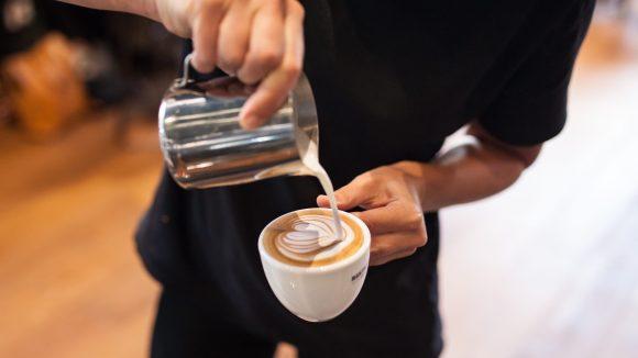 Milch wird eine Cappucino Tasse gegossen