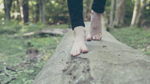 Frau balanciert barfuß über einen am Boden liegenden Baumstamm im Barfußpark und ist mit einer schwarzen Hose bekleidet.