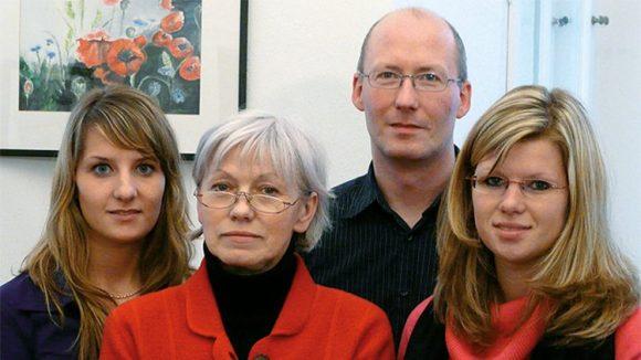 Teamfoto mit zwei jüngeren und einer älteren Frau, ein Mann im Hintergrund