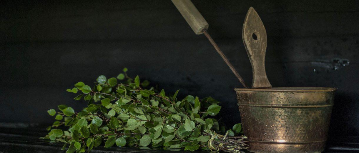 Ein Bündel Zweige neben Aufgussbehälter aus Messing auf einer Holzbank