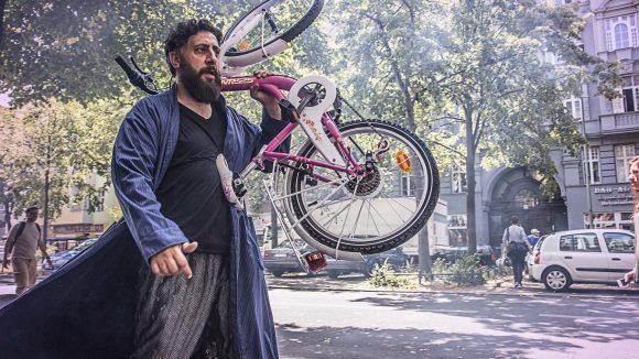 Mann trägt Kinderfahrrad durch die Stadt.