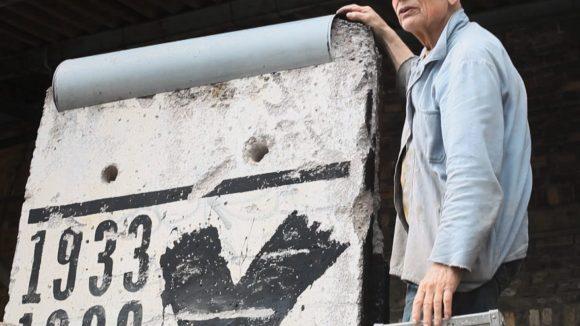 Der Aktionskünstler Ben Wagin (86) arbeitet an einem Mauerstück, um an die Jahre 1933, 1938 und 1945 zu erinnern.