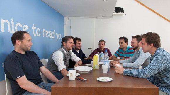 Alle an einem Tisch. Das Team von Mediaspot bei der Kaffeepause.