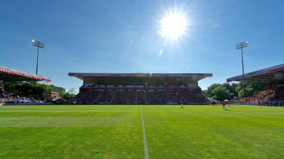 Blick auf die Tribüne des Fußballstadions Alte Försterei, im Vordergrund der Platz, links und rechts weitere Tribünen. Sonnenschein