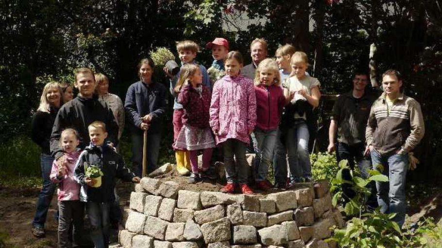 Endlich ist sie fertig: Alle fleißigen Helfer versammeln sich auf der frisch erbauten Kräuterspirale im Schulgarten der Grundschule am Ginkobaum.