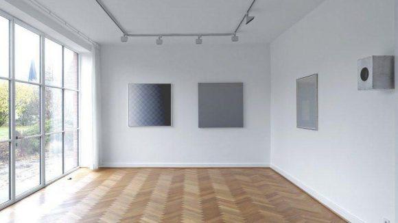 """""""Facetten von Grau"""". An der mittleren Wand hängen Exponate der Künstler Arnulf Letto (l.) und James Howell (r.). Bei der Betrachtung des Bildes von Letto wird die Wahrnehmung herausgefordert, da sich optische Täuschungen einstellen. In der Anschauung wirkt die Oberfläche räumlich."""