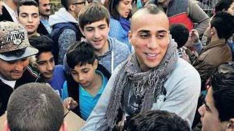 Autogramme vom Fußball-Profi. Änis Ben-Hatira spricht mit Flüchtlingskindern auf dem Bolzplatz.