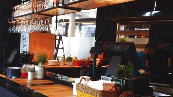 Viele Gläser überm Tresen im BagYard - hier gibt es nämlich auch Cocktails! Ansonsten: Holz, Emaille und Stil.