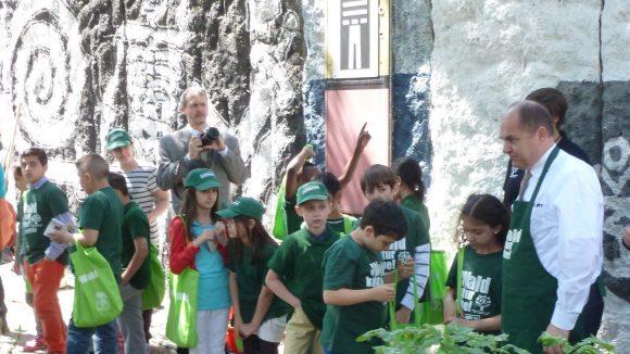 Bundesminister Schmidt lässt sich von den Kids erklären, was zusätzlich in dem angelegten Naturraum gepflanzt wurde.