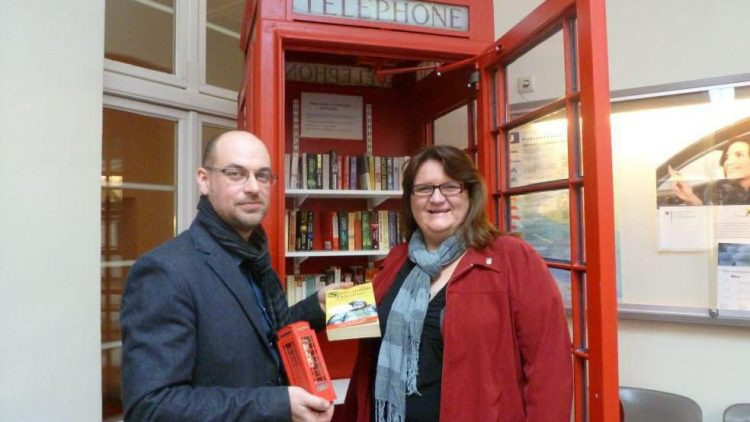 """Susanne Helbig von der Kameradschaft GSU und Bezirksstadtrat Carsten Röding vor der """"Alten Lady"""". Das rote Telefonhäuschen ist nun eine Bücherbox."""