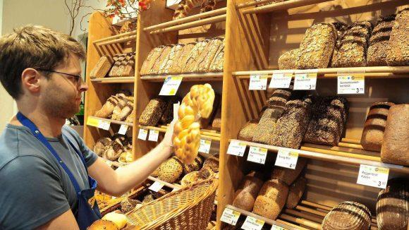 Reichhaltiges Sortiment. Naturkostfachverkäufer Cedric Quentin füllt die Regale der trotz Insolvenz weiter geführten Bäckerei in der Ufa-Fabrik.