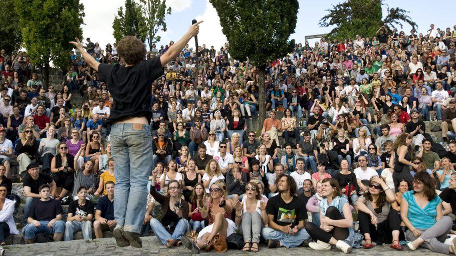 Ein Karaoke-Sänger performt vor Publikum im Mauerpark. Zwischen den Nummern hält Joe Hatchiban zur Müllentsorgung an.