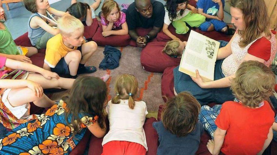 Beim Bilderbuchkino liest eine Mitarbeiterin eine Kindergeschichte vor, die mit Bildern auf einer Leinwand untermalt wird.