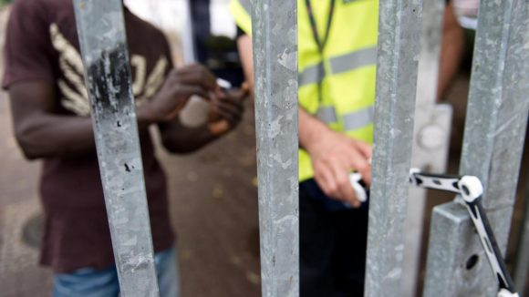 Ein Bewohner zeigt einem privaten Wachmann seinen Berechtigungsausweis, damit dieser das Tor zum Gelände der Kreuzberger Gerhart-Hauptmann-Schule in Berlin öffnet.