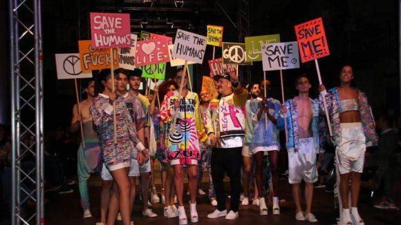 Bunt-fröhliche Demo-Gemeinde: Die Models von Tzuji wurden mit Transparenten auf den Laufsteg geschickt und unterstreichen das Motto der Alternativen Fashion Week.