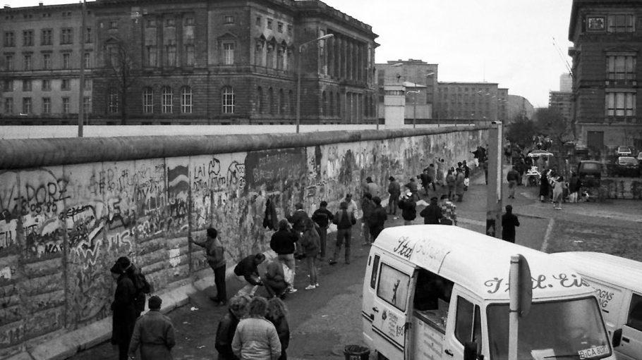 Berliner Mauer, 1989. Einen Monat nach der Öffnung besichtigen Neugierige in der Niederkirchnerstraße die von Souvernirjägern schon beträchtlich angenagte Mauer. Rechts im Anschnitt der Martin-Gropius-Bau (West), links das heutige Abgeordnetenhaus von Berlin (Ost).