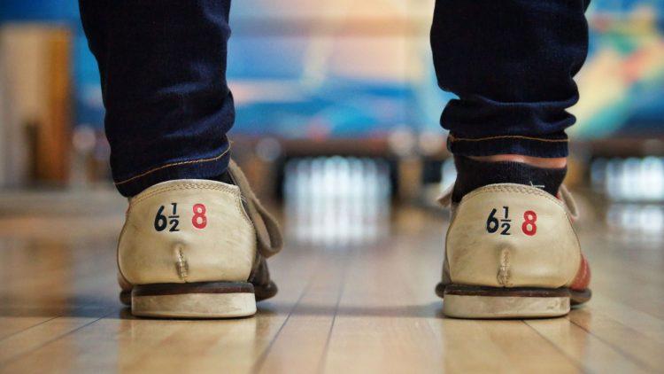 Die Füße eines Menschwen in rot-weißen Bowlingschuhen, im Hintergrund verschwommen eine Bowlingbahn