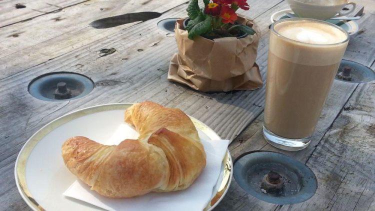 Eine alte Holzkabeltrommel wird zum natürlich schönen Tisch. So schmecken Kaffee und Croissant.