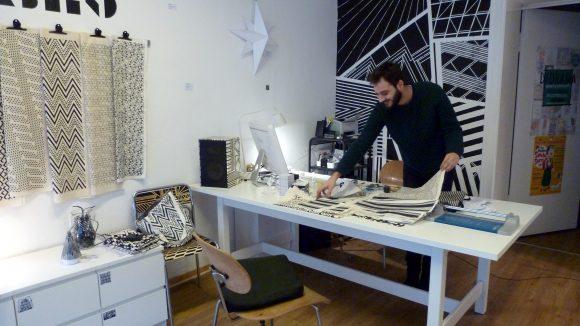 """Daniel Arab bei der Arbeit im Laden seines Labels """"colorblind patterns""""."""