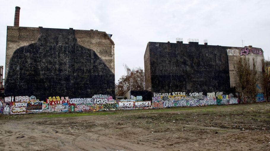 Die Mauern an der Cuvry-Brache tragen Schwarz. Der Street-Artist Blu hat dort 2014 seine Kult-Graffiti übermalt.