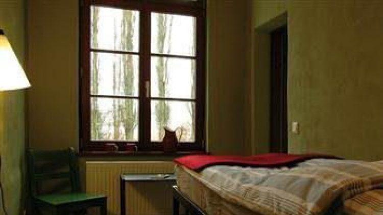 """Das neu gestaltete """"Grüne Zimmer"""" im 5raumhotel an der Rummelsburger Bucht. Nachdem im Zuge der Restaurierung der alte Putz von den Wänden entfernt wurde, kamen die Abhöranlagen der ehemaligen DDR-Haftanstalt zum Vorschein."""