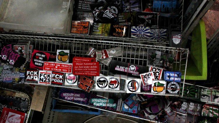 An einem grauen Nachmittag gehen die Sticker im M99 besonders gut weg. Ist ja auch für alle Facetten und Fassons des linken Spektrums was dabei: Anti-Nazi, Pro-Asyl, Pro-Tier, Anti-Pegida, Po-Polizisten, usw.