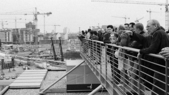Aussichtsplattform der Infobox, 1996. Die Besucher der Infobox blicken Richtung Martin-Gropius-Bau. Im Hintergrund die Baustelle um den Potsdamer Platz. Der Rohbau des vom japanischen Architekten Arata Isozaki entworfenen Gebäudes steht bereits.