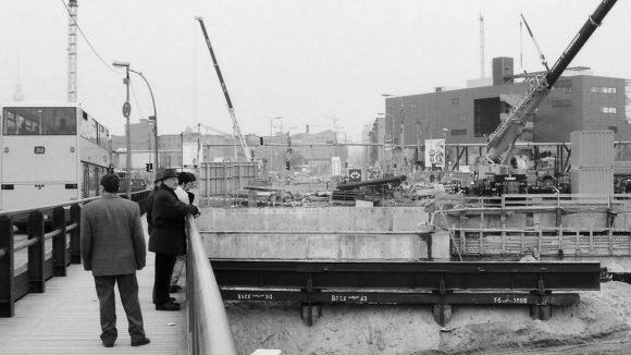 Blick vom Potsdamer Platz Richtung Leipziger Platz, 1996. Baugrube am Potsdamer Platz. Hinten rechts auf dem Leipziger Platz steht die rote Infobox. In dem auf Stelzen stehenden Bau wurde eine Ausstellung über die Bauvorhaben gezeigt, das Dach diente als Aussichtsplattform.