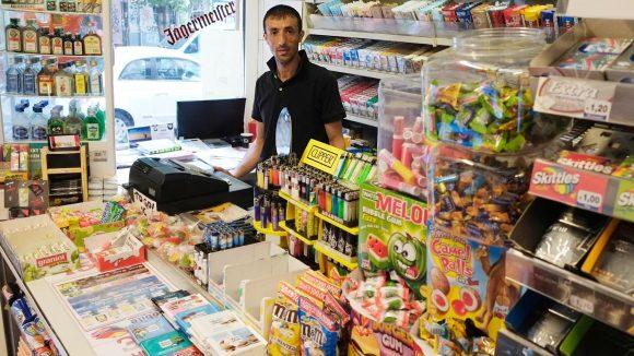 Ein Späti-Besitzer steht zwischen Tabakwaren, Schnaps und Kaugummis hinter seiner Kasse.