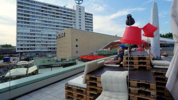 """Die Lounge """"Schöne Aussicht"""" mit Holzpaletten und Stehlampen. Hier der Blick in Richtung Bahnhof Zoo, auf den Zoo-Palast und das Hutmacher-Hochhaus am Hardenbergplatz."""