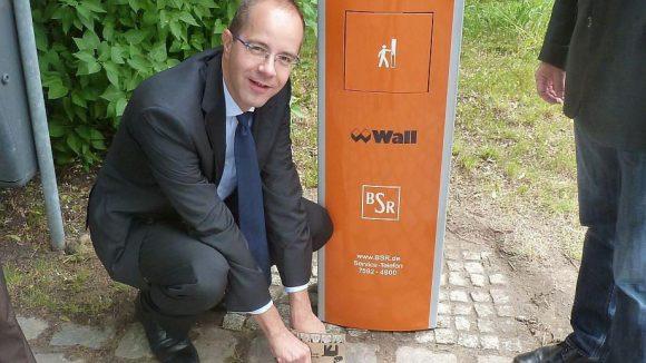 Bezirksstadtrat Gräff demonstriert den Gebrauch der patentierten Papiertüten.