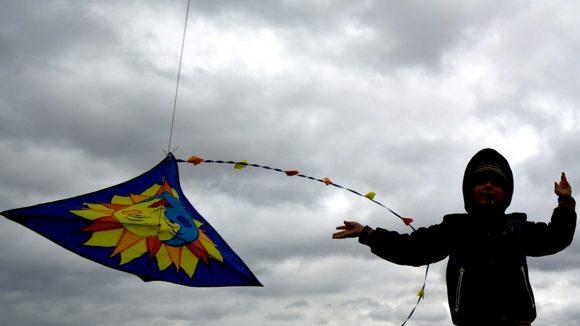 Ein Junge lässt auf dem Teufelsberg bei starkem Wind und dicht bewölktem Himmel einen Drachen steigen.
