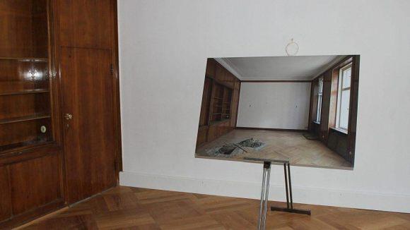 """Im 2. Stock befindet sich der sogenannte """"Hinkel-Raum"""". Hier hauste in den 1940ern Hans Hinkel, Geschäftsführer der Reichskulturkammer der Nazis. Auch die dunkle Holzvertäfelung stammt noch aus jener Epoche. Das Bild im Bild zeigt den Zustand des Raums kurz nach Ende des Hotelbetriebs 2013."""