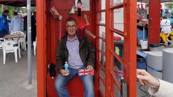 Ein Englishman in Berlin: Michael Hughes hat die rote Telefonzelle am Fehrbelliner Platz mit Souvenirs bestückt, die er für seine Fotos nutzt.